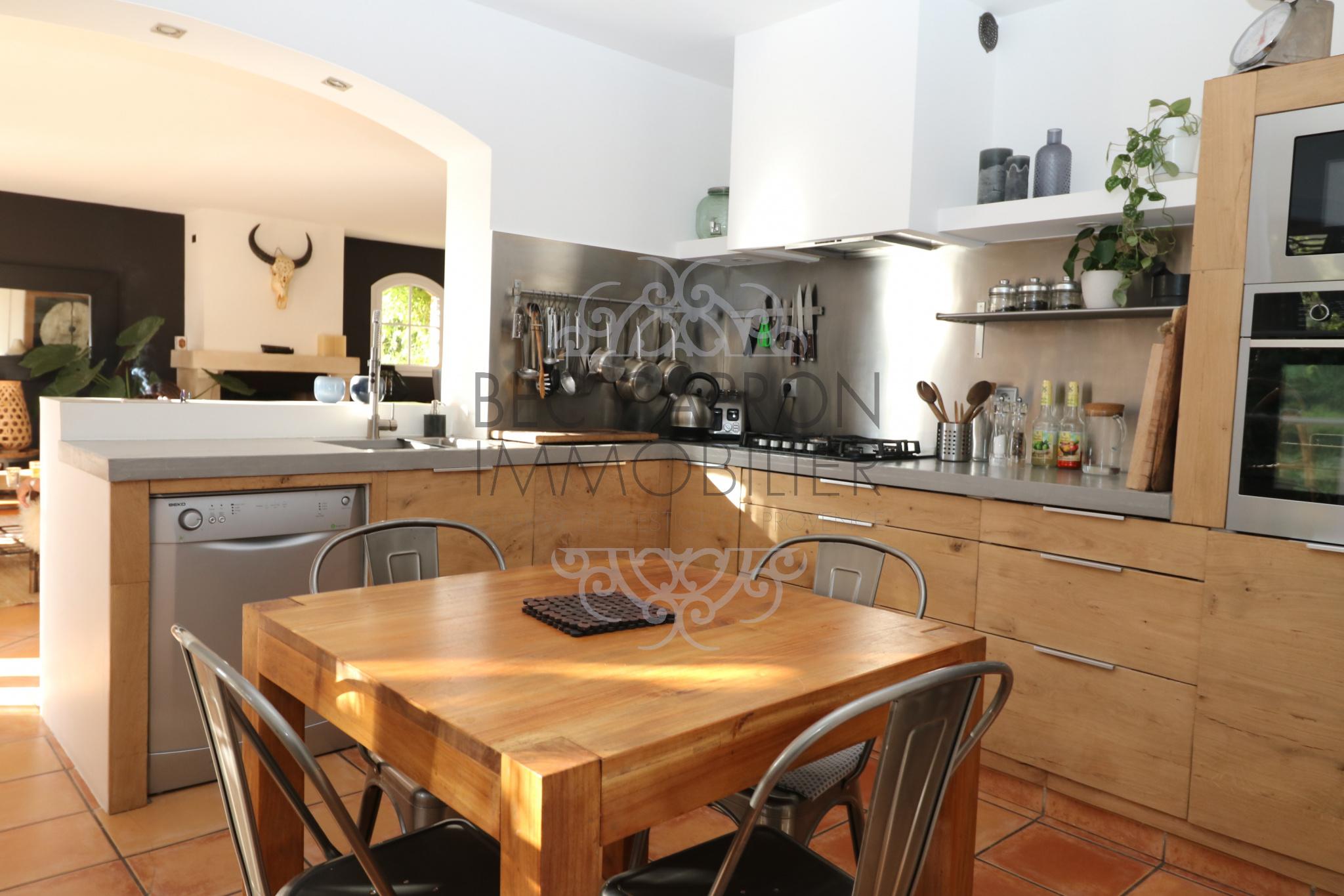Vue coté cuisine ouverte équipée en bois.