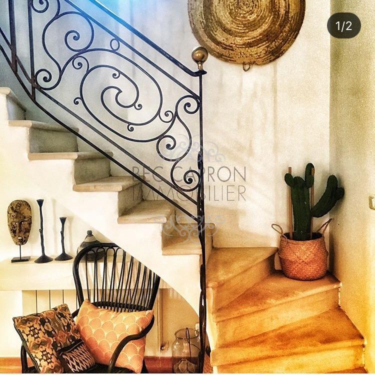 Montée d'escalier avec belle rampe en fer forgé