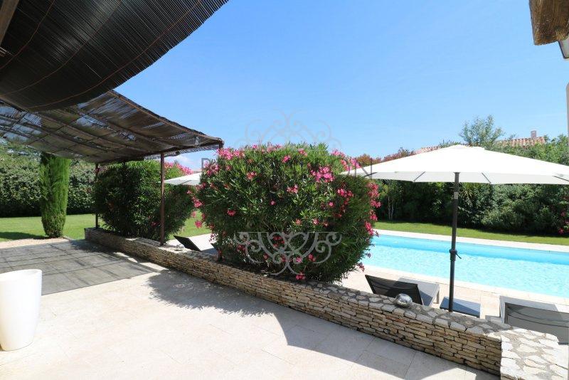 Vue de la terrasse sur le jardin végétalisé et la piscine